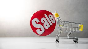 Mini shopping cart with red sale label stock photos