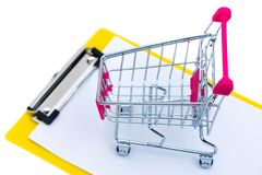 Mini shopping cart or supermarket trolley on clipboard with blan. K white paper sheet, isolated on white background, business finance shopping concept. menu Royalty Free Stock Image