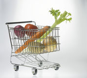 Mini Shopping Cart With Vegetables. Mini shopping cart as a vegetable basket or grocery cart holding tomato, onion, celery, carrot and potatoes in front of a Stock Photos