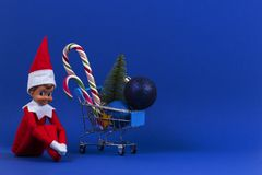 Mini Shopping Cart With Candy Canes, Little Christmas Tree, Xmas Decoration Bauble Balls And Toy Santa Elf On Navy Blue Stock Photography