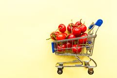 Mini shopping grocery cart full of fresh cherries Fresh berries on yellow background. Healthy summer food concept royalty free stock photo