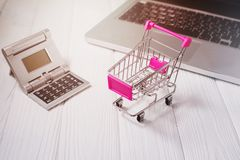 Mini shopping trolley, laptop, calculator on a white wooden desk Royalty Free Stock Photography
