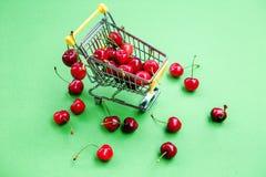 Mini shoppingcart avec les cerises mûres rouges Photographie stock libre de droits