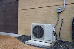 Mini sistema spaccato del condizionatore d'aria accanto alla casa con il muro di mattoni immagini stock libere da diritti