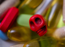 Mini-skull surrounded by pills Stock Photography