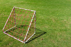 Mini small football goal for children with red net on the green. Yard in day light royalty free stock images