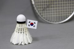 Mini South Korea flag stick on the white shuttlecock on the grey background and out focus badminton racket. Concept of badminton sport stock photos