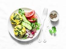 Mini- spenatcheddarfrittata och grönsaksallad på ljus bakgrund, bästa sikt Lekmanna- lägenhet för frukosttabell fotografering för bildbyråer