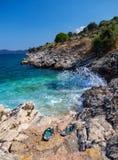 Mini spiaggia e Flip-flop con una bella vista sull'isola di Kefalonia nel Mar Ionio in Grecia immagini stock libere da diritti