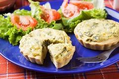 Mini spinach quiche with salad. Mini spinach quiche served with tomato and lettuce salad Stock Photos