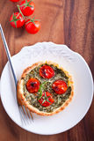 Mini Spinach Quiche with tomato served on a plate. Royalty Free Stock Photo