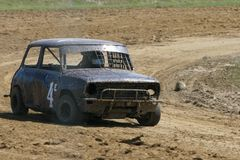 Mini Stock car. Small saloon stock car racing on a dirt track.  Could be leader, or back marker.  At a speedway track in New Zealand Stock Photo