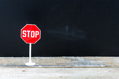 Mini STOP Sign Over Chalkboard Background And Table Royalty Free Stock Photography