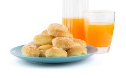 Mini sugary donuts in blue dish with orange juice Stock Photos