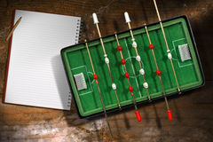 Mini Table Football Game with a Notebook. Top view of mini table football game with empty notebook and pencil. On a wooden table with shadows Stock Images