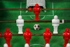 Mini Table Football Game with Soccer Ball. Macro photo of a mini table football game with an old black and white soccer ball Stock Photo