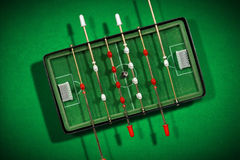 Mini Table Football Game with Soccer Ball. Top view of mini table football game with an old black and white soccer ball. On a green background with shadows Stock Photos