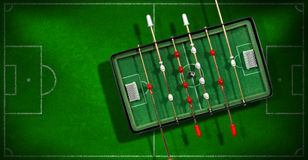 Mini Table Football Game with Soccer Ball. Top view of mini table football game with an old black and white soccer ball. On a green soccer field with shadows Stock Photography