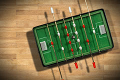 Mini Table Football Game with Soccer Ball. Top view of mini table football game with an old black and white soccer ball. On a wooden floor (parquet Stock Image