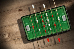 Mini Table Football Game with Soccer Ball. Top view of mini table football game with an old black and white soccer ball. On a wooden table with shadows Stock Photo