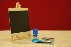 Mini tableau noir, tampon en caoutchouc rond, agrafeuse, ciseaux, stylo de boule et règle Images stock