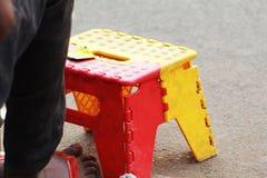 Mini taburete del color rojo y amarillo y una pierna humana foto de archivo libre de regalías