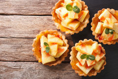 Mini Tart with pineapple and mint close-up. horizontal top view. Mini Tart with pineapple and mint close-up on the table. horizontal view from above stock images