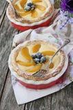 Mini tarta con el relleno, el melocotón y los arándanos del queso cremoso Fotografía de archivo libre de regalías