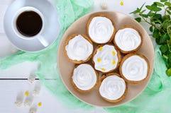 Mini tarta z lotniczą śmietanką na talerzu i filiżance kawy na białym drewnianym tle Zdjęcia Royalty Free