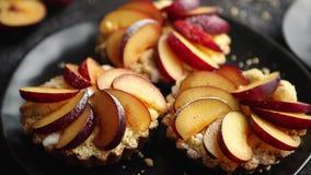 Mini tartes faites maison délicieuses avec le fruit coupé en tranches frais de prune banque de vidéos