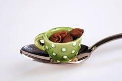 Mini taza de café con los granos de café en la cuchara del té fotos de archivo libres de regalías