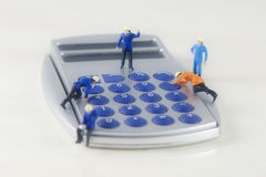 Mini technicians repairing. A calculator royalty free stock images