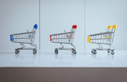 Mini three shopping cart or supermarket trolley empty on table,Finance and money shopping concept. Mini three shopping cart or supermarket trolley empty on white Stock Photo