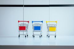Mini three shopping cart or supermarket trolley on table,Finance and money shopping concept. Mini three shopping cart or supermarket trolley on white table Royalty Free Stock Photos