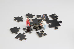 Mini tiny builders at puzzle construction site Stock Images