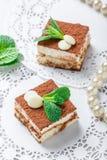 Mini tiramisu de gâteaux avec du chocolat, le cacao et les sucreries blancs sur la fin légère de fond  Dessert et friandise délic Photos libres de droits