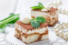 Mini tiramisu de las tortas con el chocolate, el cacao y los caramelos blancos en cierre ligero del fondo para arriba Barra delic Imagenes de archivo