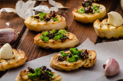 Mini toasts with garlic and dried tomato Stock Photo