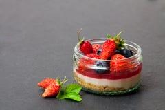 Mini torta di formaggio selvaggia delle bacche della foresta in un vaso di vetro sullo sto nero Fotografia Stock