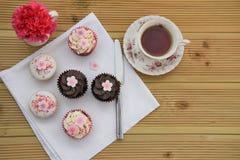 Mini tortas del chocolate con las decoraciones y el espacio rosados helados de la flor Foto de archivo