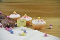 Mini tortas del chocolate delicioso con las decoraciones del huevo y palabras o texto felices de Pascua Fotos de archivo