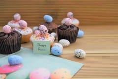 Mini tortas del chocolate delicioso con las decoraciones del huevo y palabras o texto felices de Pascua Foto de archivo