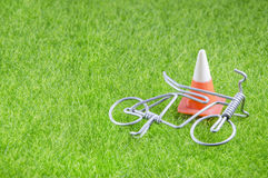 Mini toy bicycle and traffic cone on a grass Royalty Free Stock Image