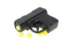 Mini toy gun. With yellow pellets on white background Royalty Free Stock Photos
