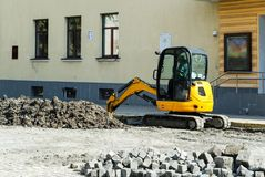Mini tractor digger. Tractor digger is digging a trench for the installation of water pipes stock image