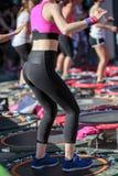Mini Trampoline Workout: Flickor som gör kondition, övar i utomhus- grupp på idrottshallen Arkivbild