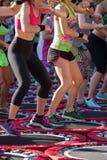 Mini Trampoline Workout: Flickor som gör kondition, övar i utomhus- grupp på idrottshallen Royaltyfri Foto