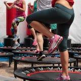 Mini Trampoline Workout: Mädchen, das Eignungs-Übung in der Klasse an der Turnhalle tut Stockfoto