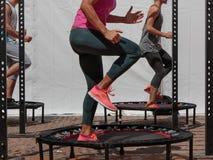 Mini Trampoline Workout: Menina que faz o exercício da aptidão na classe em Imagens de Stock