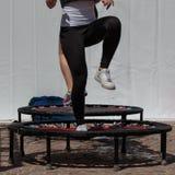 Mini Trampoline Workout: Menina que faz o exercício da aptidão na classe em Imagem de Stock Royalty Free
